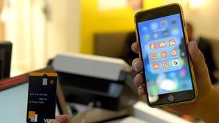 Un client tient une carte bancaire Orange Bank ainsi qu'un smartphone sur lequel est installé l'application de la banque en question, en ligne depuis le 2 novembre 2017. (ERIC PIERMONT / AFP)