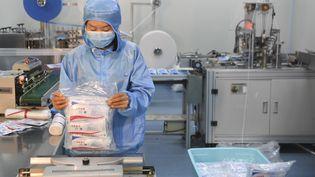 Un salarié emballe des masques dans une entreprise de production de masques, àChongqing, en Chine, le 11 février 2020. (WANG QUANCHAO / XINHUA / AFP)