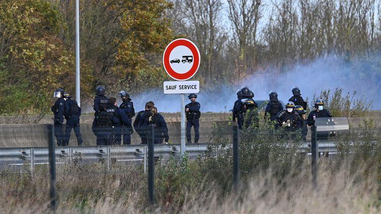 Des policiers utilisent du gaz lacrymogène pour faire reculer des migrants sur l'A16, le 19 novembre 2020, à Calais (Pas-de-Calais). (DENIS CHARLET / AFP)