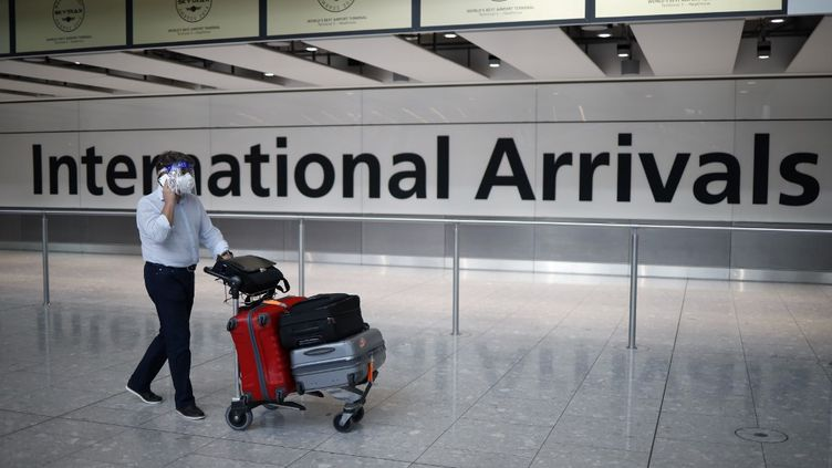 Un passager arrive à l'aéroport d'Heathrow, à Londres, le 22 mai 2020. (TOLGA AKMEN / AFP)