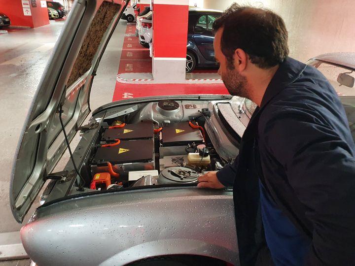 Sous le capot de cette Peugeot 504 coupé, datant de 1971, le moteur essence a été remplacé par des batteries électriques. (BORIS HALLIER / RADIO FRANCE)