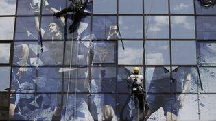 Les effigies des joueurs de l'équipe de France de football sont retirées de la façade du siège de la Fédération française de football, après l'échec de l'Euro 2012, le 28 juin 2012. (KENZO TRIBOUILLARD / AFP)