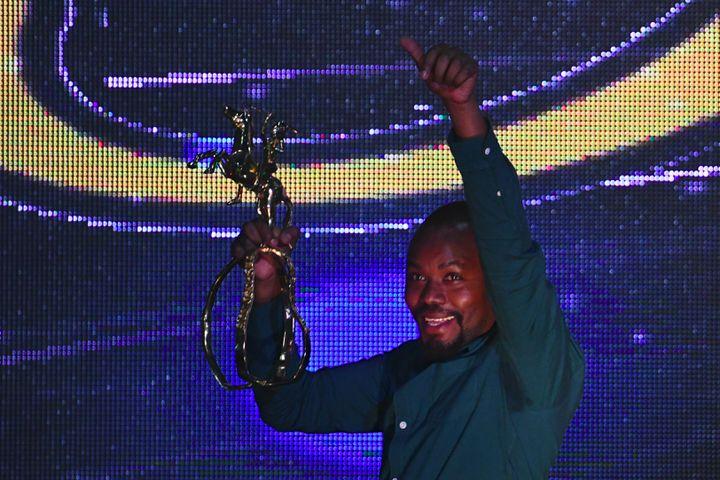 """Le cinéaste rwandais Joël Karekezi brandit l'Etalon d'or de Yennenga qu'il a remporté pour son film, """"La Miséricorde de la jungle"""", lors de la cérémonie de clôture du Fespaco le 2 mars 2019, à Ouagadougou (Burkina Faso). (ISSOUF SANOGO / AFP)"""