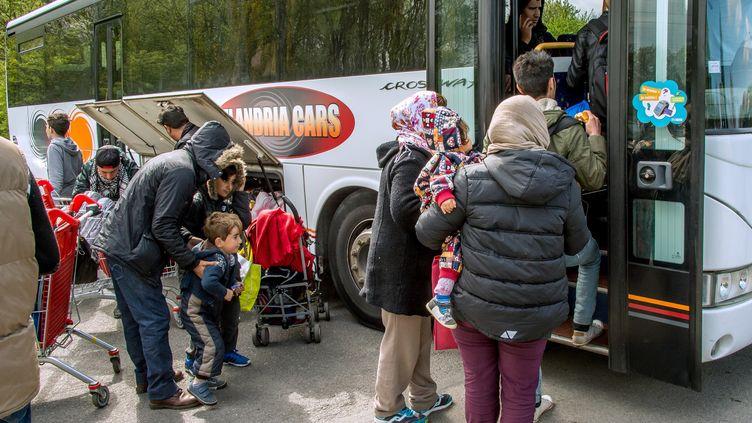 Des migrants montent dans des bus, le 14 avril 2017, après l'incendie du camp de Grande-Synthe (Nord). (PHILIPPE HUGUEN / AFP)