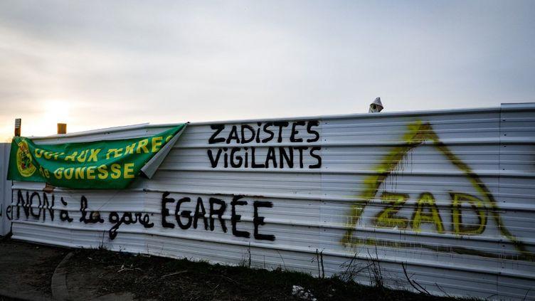 Des tags contre un projet de gare sur une palissade à l'entrée du Triangue de Gonesse, dans le Val-d'Oise, le 13 février 2021. (GEOFFROY VAN DER HASSELT / AFP)