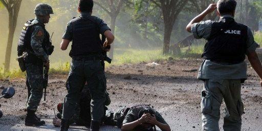 Province deNarathwat, le 18 février 2014. Des policiers et des démineurs thaïlandais sur le lieu d'un attentat à la bombe attribué à des séparatistes. ( AFP PHOTO / MADAREE TOHLALA)