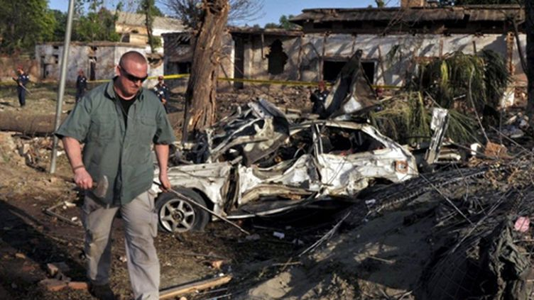 Un officiel américain examine les lieux après la tentative d'attaque contre le consulat des Etats-Unis à Peshawar (AFP - A. MAJEED)