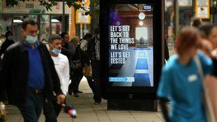 """Des piétons passent devant un panneau d'affichage faisant la promotion du programme de suivi des coronavirus du NHS (National Health Service) britannique """"Test and Trace"""", à Manchester, dans le nord-ouest de l'Angleterre, le 3 août 2020. (OLI SCARFF / AFP)"""