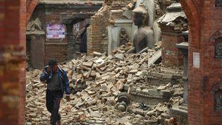 Un homme pleure, dimanche 26 avril 2015, près des ruines d'un temple après le séisme qui a touché le Népal la veille, àBhaktapur, près de Katmandou. (NAVESH CHITRAKAR / REUTERS)