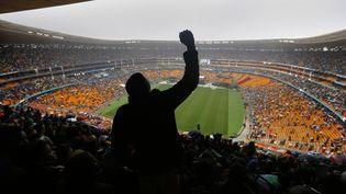 Un homme lève le poing lors du discours de Barack Obama dans le stade deJohannesburg (Afrique du Sud), le 10 décembre 2013, où se tient la cérémonie d'hommage à Nelson Mandela. (YANNIS BEHRAKIS / REUTERS)