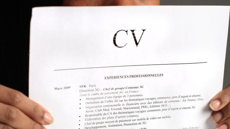 Une jeune femme tient son CV devant son visage, le 8 janvier 2011. (MAXPPP)