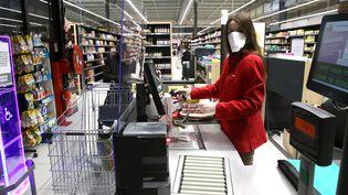 Une caissière équipée d'un masque de protection et derrière une vitre en Plexiglas encaisse les achats d'une cliente à Auch (Gers), le 17 mars 2020. (SEBASTIEN LAPEYRERE / HANS LUCAS / AFP)