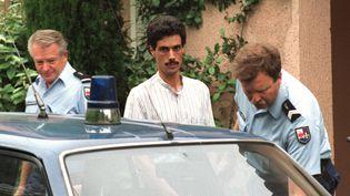 Omar Raddad, le jardinier de Ghislaine Marchal, monte dans une voiture de gendarmerie, le 26 juin 1991. (GERARD JULIEN / AFP)