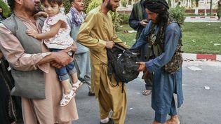 Un combattant taliban fouilles les sacs de personnes sortant de l'aéroport Hamid Karzai de Kaboul en Afghanistan. (WAKIL KOHSAR / AFP)