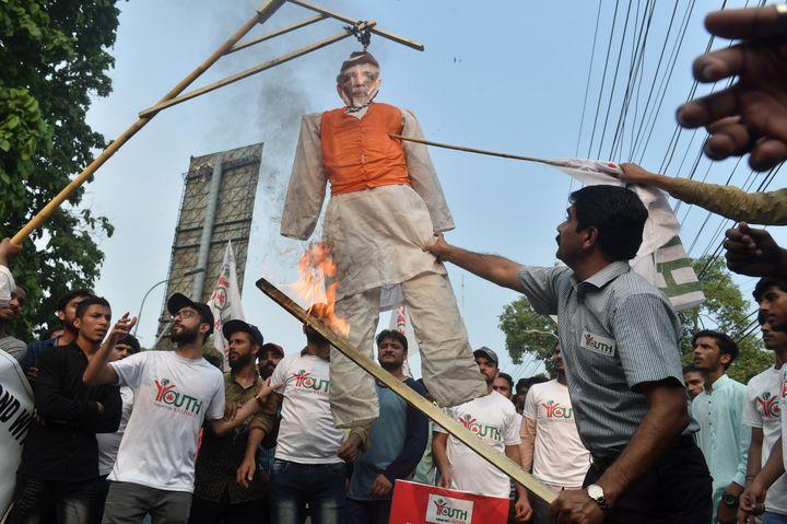 Des manifestants pakistanais brûlent un mannequin à l'effigie du Premier ministre indien Narendra Modi, le 5 août à Lahore, deuxième plus grande ville du Pakistan. (ARIF ALI / AFP)