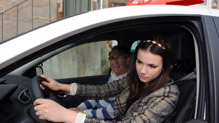 Une jeune femme prend un cours de conduite avec un moniteur d'auto-école, le 19 mars 2012 au Mans. (JEAN-FRANCOIS MONIER / AFP)