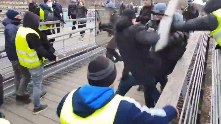 """Capture d'écran d'une vidéo postée le 5 janvier 2019 sur Twitter par Line Press, où l'on voit un individu boxer un CRS lors de """"l'acte 8"""" des """"gilets jaunes"""" à Paris. (LINE PRESS / TWITTER)"""
