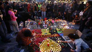 Des personnes posent des bougies en hommage aux victimes des attentats, le 22 mars 2016 à Bruxelles. (CHARLES PLATIAU / REUTERS)