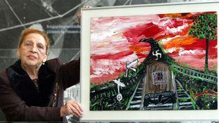 L'écrivain, peintre et musicienne rom Ceija Stojka, déportée à dix ans, montre un de ses tableaux (2003)  (Rainer Jensen / DPA / AFP)