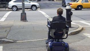 Une personne handicapée traverse la rue avec un quadriporteur, le type de fauteuil roulant sur lequel un jeune Norvégien a été arrêté en état d'ivresse, en décembre 2013. (ANDRES BALCAZR  / E+ / GETTY IMAGES )