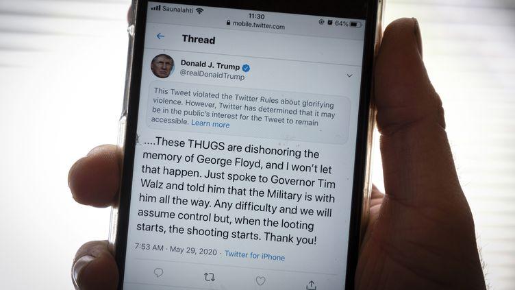 Un tweet posté par Donald Trump après la mort de George Floyd, accompagné d'un message de Twitter indiquant que le contenu du texte violait le règlement du réseau social concernant l'apologie de la violence, le 29 mai 2020. (OLIVIER MORIN / AFP)