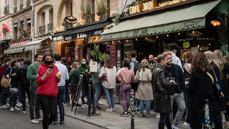 Des Parisiens profitent des températures clémentes dans la capitale, le 21 février 2021, rue de Buci (6e arrondissement). (BERTRAND GUAY / AFP)
