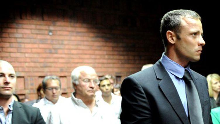 Oscar Pistorius dans le tribunal, avec derrière lui son frère et son père