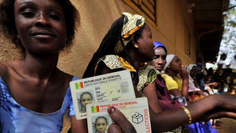 Une Sénégalaise montre sa carte d'identité et sa carte d'électeur. (ISSOUF SANOGO / AFP)