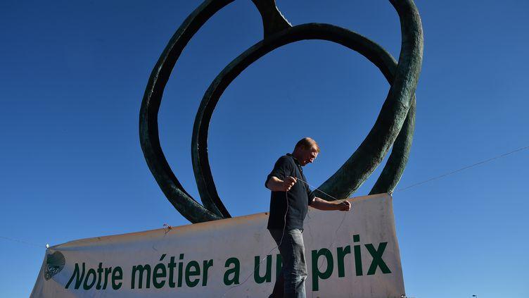 Philippe Jehan, le président de la FDSEA, installe une affiche devant le siège de Lactalis. (JEAN-FRANCOIS MONIER / AFP)