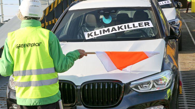 Un militant de Greenpeace bloque le déchargement de voitures SUV àBremerhaven en Allemagne, le 7 septembre 2019. (PICTURE ALLIANCE / PICTURE ALLIANCE)