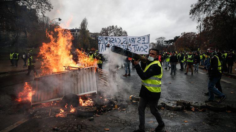 """Les """"gilets jaunes"""" à côté d'une barricade à Paris, le 1er décembre 2018. (ABDULMONAM EASSA / AFP)"""