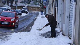 Un homme déblaie la neige tombée devant chez lui, le 13 janvier 2017, à Saint-Symphorien-sur-Coise (Rhône). (MAXPPP)