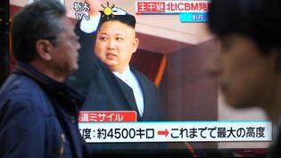 Dans une rue de Séoul, en Corée du Sud, la télévision sud-coréenne annonce le nouveau tir de missile du régime nord-coréen, le 29 novembre 2017. (KAZUHIRO NOGI / AFP)