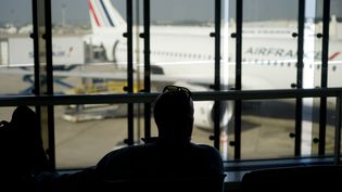 Un passager de dos contemple un avion de la compagnie Air France, le 15 septembre 2014. (Photo d'illustration) (KENZO TRIBOUILLARD / AFP)