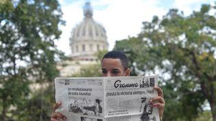 Un jeune homme lit le journal officiel Granma, le 26 novembre 2016, au lendemain de la mort de Fidel Castro, à La Havane (Cuba). (ARTUR WIDAK / NURPHOTO / AFP)