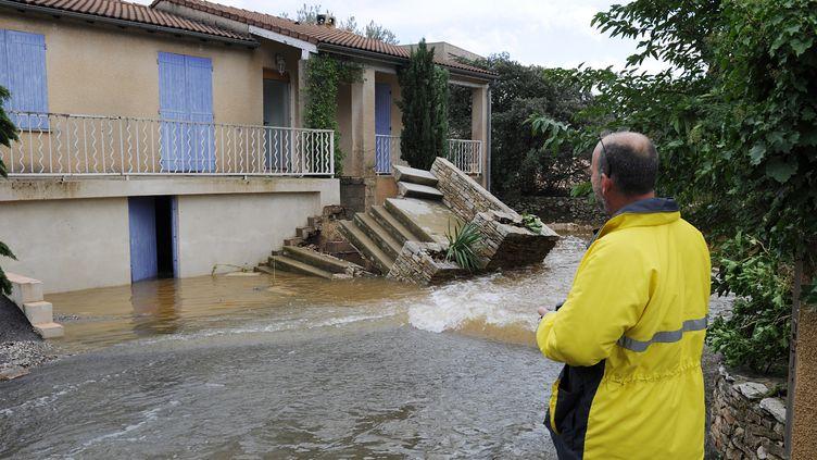 Un homme observe sa maison, à Nîmes, le 10 octobre 2014. (BORIS HORVAT / AFP)