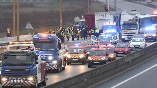 Des secouristes sur l'autoroute A13 après un carambolage impliquant sept véhicules, à hauteur d'Epône (Yvelines), le 30 janvier 2017. (LIONEL BONAVENTURE / AFP)