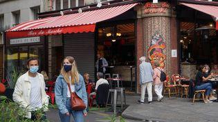 A Paris, un couple masqué se promène dans le 6e arrondissement, le 30 août 2020. (MYRIAM TIRLER / AFP)
