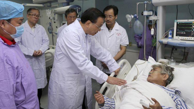 Le Premier ministre chinois Li Keqiang parle à un patient, dans un hôpital de Jianli (province de Wuhan), le 2 juin 2015. (REUTERS / cnsphoto CHINA OUT)