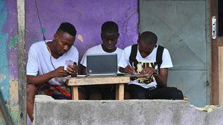 De jeunes Ivoiriens surfent sur internet dans le quartier populaire d'Abobo, à Abidjan (Côte d'Ivoire), le 14 février 2020. (ISSOUF SANOGO / AFP)