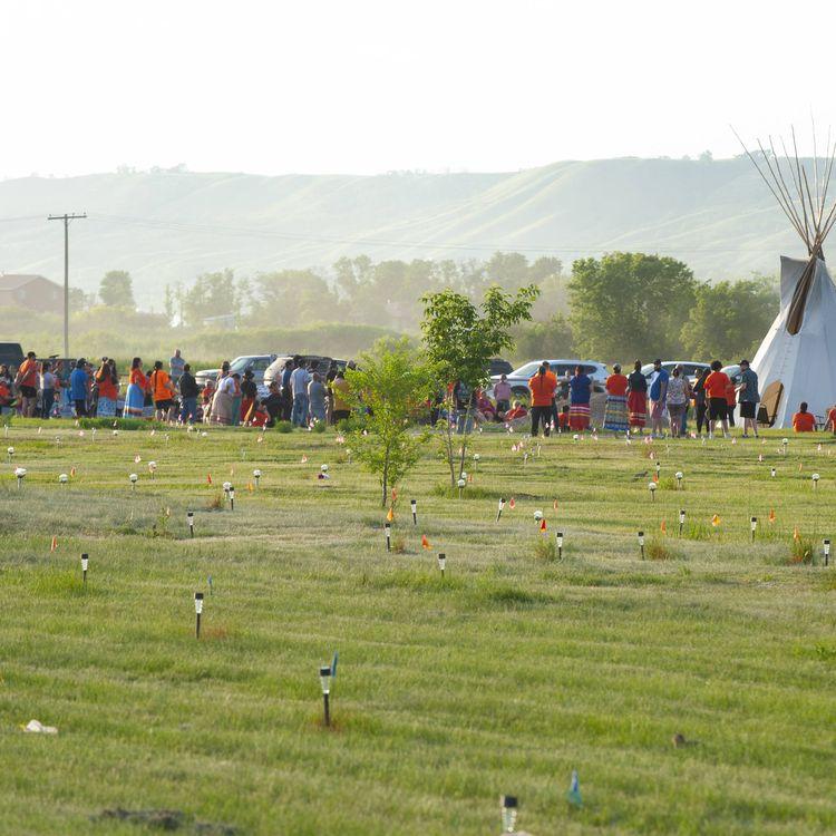 Un hommage est rendu sur le site de la détection de 751 tombes anonymes, marquées par des drapeaux et des lampes, près d'un ancien pensionnat catholique pour autochtones à Marieval (Canada), le 26 juin 2021. (MARK TAYLOR/AP/SIPA)