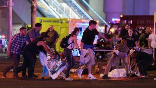 Une personne blessée par la fusillade à Las Vegas (Nevada, Etats-Unis) est transportée par d'autres, le 2 octobre 2017. (ETHAN MILLER / GETTY IMAGES NORTH AMERICA)
