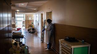 Une soignante dans un couloir de l'hôpital Saint-Louis, à Paris, en mai 2020. (MARTIN BUREAU / AFP)