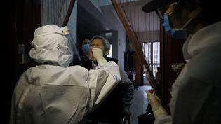 Une habitante de Wuhan (Chine), épicentre de l'épidémie, se soumet à un test de dépistage du Covid-19, le 14 mai 2020. (STR / AFP)