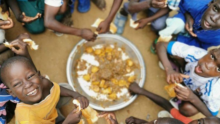 """Des enfants talibés prennent leur repas grâce à un réseau de femmes mis en place par l'association Les petites gouttes. (Photo/M.Fall/ Association """"les petites gouttes"""")"""