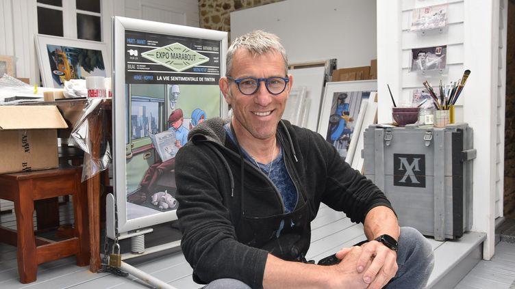 L'artiste peintre Xavier Marabout dans son atelier d'Auray, devant des oeuvres de série Hergé-Hopper, en mai 2021. (MATHIEU PELICART / MAXPPP)