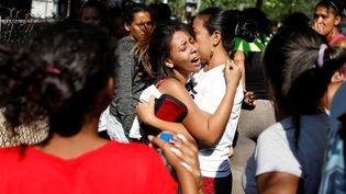 Des proches de détenus du commissariat de Valence (Venezuela) apprennent qu'au moins 68 prisonniers sont morts lors d'une mutinerie. (CARLOS GARCIA RAWLINS / REUTERS)