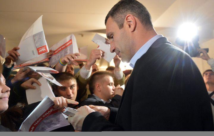 Vitali Klitschko signe des autographes à la sortie d'un meeting, le 15 octobre 2012 à Kiev, en Ukraine. (SERGEI SUPINSKY / AFP)
