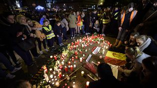 Des personnes sont rassemblées autour de bougies et de fleurs à l'aéroport de Bruxelles à Zaventem (Belgique), le 23 mars 2016. (YORICK JANSENS / BELGA / AFP)