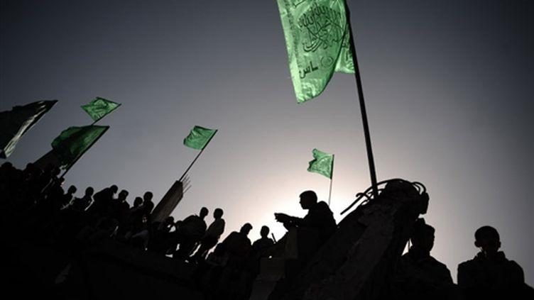Militants du Hamas brandissant le drapeau du mouvement sur des ruines à Gaza après les bombardements israéliens (© AFP/OLIVIER LABAN-MATTEI)